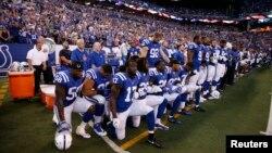 فٹ بال کے کھلاڑی صدر ٹرمپ کے تبصرے پر برہمی کے اظہار کے لیے قومی ترانے کے دوران گھٹنوں کے بل بیٹھے ہوئے ہیں۔ 24 ستمبر 2017