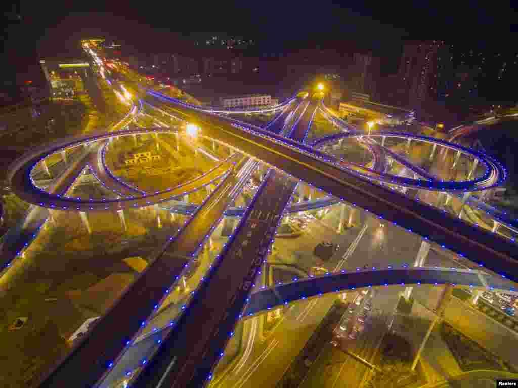 ស្ពានអាកាសមួយត្រូវបានគេបំភ្លឺភ្លើងពណ៌ខៀវ ក្នុងពេលល្ងាចដែលមានអ័ព្ទមួយនៅក្នុងក្រុង Jinan ខេត្ត Shandong ប្រទេសចិន កាលពីថ្ងៃទី២៨ ខែធ្នូ ឆ្នាំ២០១៥។
