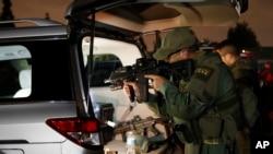 Một nhân viên Cục Rượu, Thuốc lá, Súng và Chất nổ (ATF) kiểm tra súng trước một vụ lục soát tại Los Angeles ngày 17/5/2017.