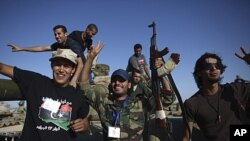 NTC fighters celebrate after capturing an armored vehicle in Wadi Dinar, Libya, Sept. 21, 2011.