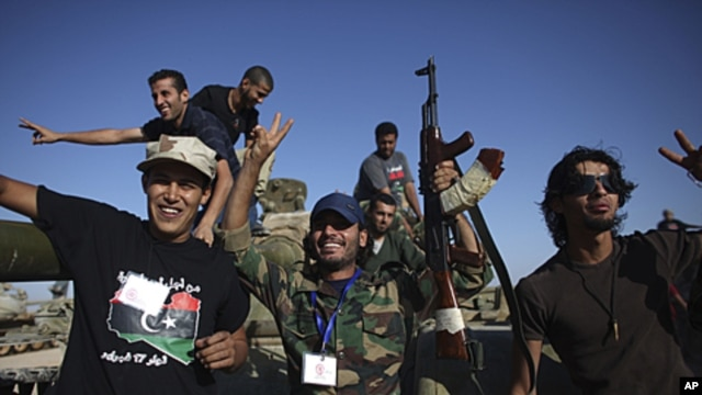 Transitional government fighters celebrate after capturing an armored vehicle in Wadi Dinar, Libya, September 21, 2011.