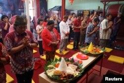 """Warga berdoa bersama dalam perayaan Tahun Baru Imlek bernuansa tradisional, """"Tumpengan Imlek"""", di sebuah vihara di Yogyakarta, 23 Januari 2020. (Foto: Antara via Reuters)"""