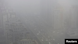 FILE - Cars drive on the Three Ring Road amid the heavy haze in Beijing.