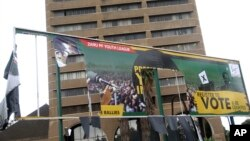 FILE - An old ripped election banner bearing a portrait of ousted President Robert Mugabe hangs outside the headquarters of the ruling ZANU PF building in Harare, Nov. 19, 2017.