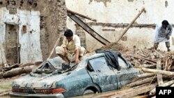 Người Pakistan ngồi trên nóc xe bị hư hỏng trước căn nhà bị sụp đổ vì lũ lụt ở Nowshera