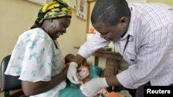 Một bà mẹ người Kenya đưa con đi chích ngừa sốt rét trong chương trình thử nghiệm