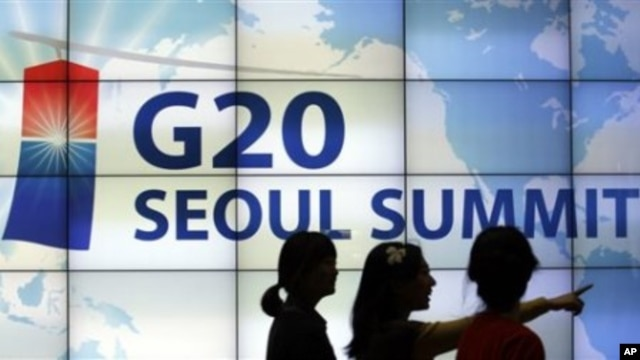 Women walk by a screen showing G20 Seoul Summit sign at the venue for the upcoming summit meeting, 02 Nov 2010