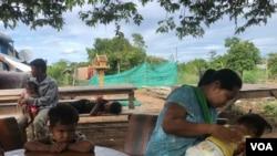 ນາງແລງ ຈັນທູນ, ອາຍຸ 35 ປີ ຊາວບ້ານຄຳປອງ ທຳ ຂອງແຂວງ ກຣາແຢ, ເບິ່ງແຍງລູກສາວຂອງລາວ ຜູ້ທີ່ຖືກວິນິໄສ ເປັນໄຂ້ເລືອດອອກ, ໃນຂະນະທີ່ ລູກນ້ອຍຮາກຢູ່ນັ້ນ ໃນລະຫວ່າງ ນາງແລງ ໃຫ້ສຳພາດກັບ ວີໂອເອ, ເມື່ອເດືອນມິຖຸນາ 2019. (Sun Narin/VOA Khmer)