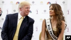 FILE - Donald Trump (L) and 2014 Miss Universe, Gabriela Isler, of Venezuela, talk during a news conference Oct. 2, 2014, in Doral, Florida.