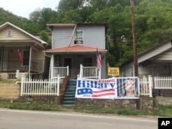 "Brenda Horvath displays a large sign that reads, ""Hillary for Prison 2016,"" on the front of her home in Logan, West Virginia, May 10, 2016. A registered Democrat who comes from long line of coalminers, she says she's supporting Donald Trump. ""When I was growing up, it was a big to-do to change from Democrat to Republicans. Now, I don't see any difference. ... They'll all out for themselves."""