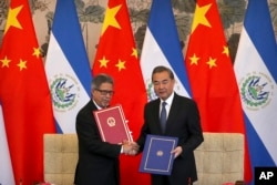 FILE - El Salvador's Foreign Minister Carlos Castaneda, left, and China's Foreign Minister Wang Yi shake hands at a signing ceremony to mark the establishment of diplomatic relations between the two countries at the Diaoyutai State Guesthouse in Beijing, Aug. 21, 2018.