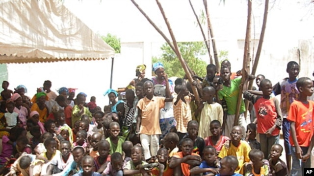 Kids from nearby villages gather at the Mbosse health clinic to watch a play on malaria prevention