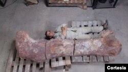 El investigador Pablo Puerta se acostó junto a un trozo de fémur del titanosaurio para dar una idea de su tamaño.