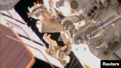 FILE - Two Russian cosmonauts are seen working outside the International Space Station during a spacewalk in this still image taken from NASA handout video, August 16, 2013.