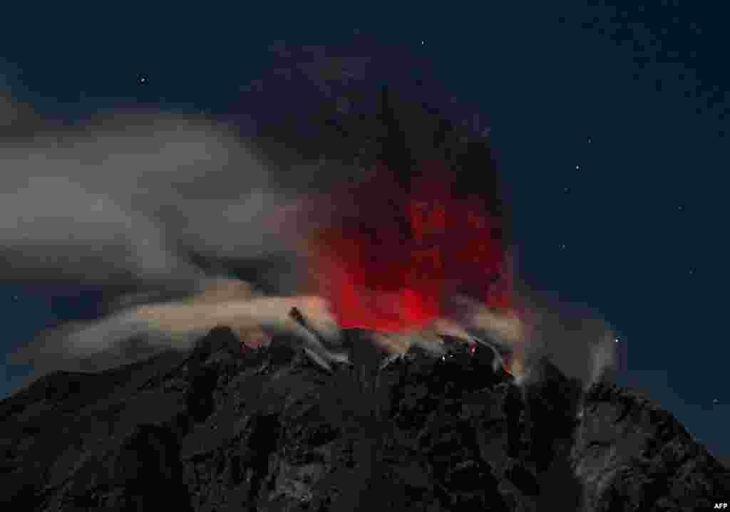 Mount Sinabung volcano spews reddish smoke and ash, as seen from the Karo district in North Sumatra province, Indonesia.