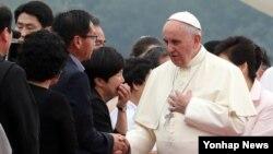 14일 한국 서울공항에 도착한 프란치스코 교황이 환영나온 인사들 중 세월호 유가족 대표들과 인사하며 위로의 말을 전하고 있다.