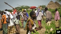 Warga desa terlihat membawa tombak di jalanan setelah menyaksikan jenazah para korban serangan suku Pokomo (tidak ada dalam gambar), menyusul bentrokan antar etnis di desa Kipao, di sekitar sungai Tana, Kenya (21/12).