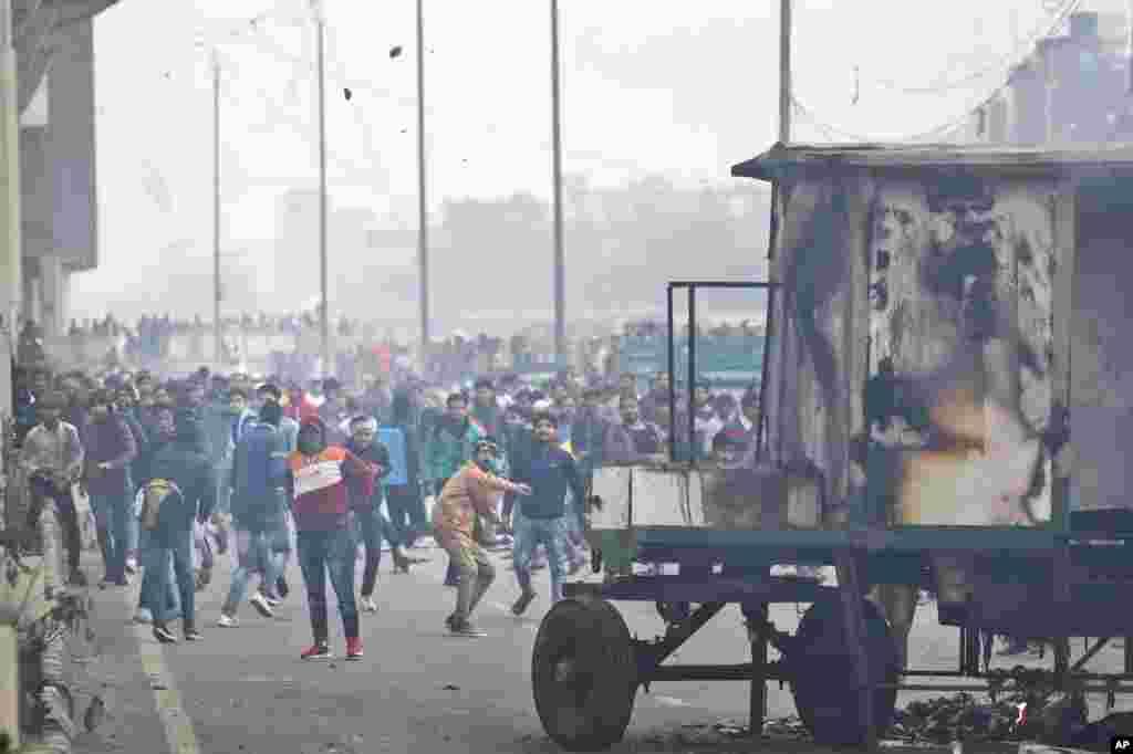 معترضان به قانون جدید شهروندی هند، در یکی از محله های دهلی نو به سمت پلیس سنگ پرتاب می کنند. پلیس با شلیک گاز اشک آور سعی در پراکنده کردن آنها دارد.
