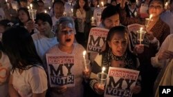 "Members of the ""White Shirt"" movement hold a candlelight vigil to demand democratic elections and political reforms in Bangkok, Thailand, Jan. 24, 2014."