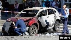 Следователи изучают обломки автомобиля на весте взрыва, где погиб Павел Шеремет. Киев, Украина. 20 июля 2017 г.