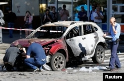 FILE - Investigators inspect a damaged car at the site where journalist Pavel Sheremet was killed by a car bomb in central Kiev, Ukraine, July 20, 2016.