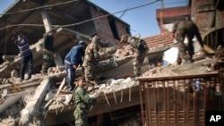 Soldados indios y residentes remueven escombros de un edificio dañado por el terremoto en Imphal, capital del nororiental estado indio de Manipur, el lunes, 4 de enero de 2016.