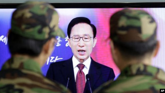 South Korean soldiers watch South Korean President Lee Myung-bak speaking to the nation during his New Year's speech,  Jan. 3, 2011.