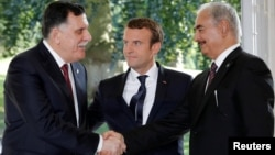 FILE - French President Emmanuel Macron stands between Libyan Prime Minister Fayez al-Sarraj (L), and General Khalifa Haftar (R), commander in the Libyan National Army (LNA), who shake hands after talks over a political deal to help end Libya's crisis in La Celle-Saint-Cloud near Paris, France, July 25, 2017.