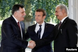 French President Emmanuel Macron stands between Libyan Prime Minister Fayez al-Sarraj (L), and General Khalifa Haftar (R), commander in the Libyan National Army (LNA), who shake hands after talks over a political deal to help end Libya's crisis in La Celle-Saint-Cloud near Paris, July 25, 2017.