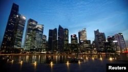 FILE - FILE - People walk past the skyline of Marina Bay central business district in Singapore.