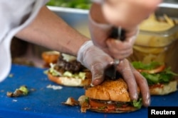 FILE - French burgers are prepared at 'Le Refectoire' food truck in Paris, Nov. 16, 2012.