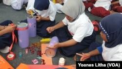 Para pelajar tingkat Sekolah Dasar ikut lomba menghias celengan dalam rangkaian kegiatan Hari Anak Nasional di Sigi, Sulawesi Tengah, 18 Juli 2019. (Foto: VOA / Yoanes Litha)