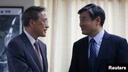 Junichi Ihara (kiri) juru runding nuklir Jepang untuk Korea Utara berjabat tangan dengan mitranya dari Korea Selatan Cho Tae-yong di Seoul (22/8/2013). Pemimpin Jepang dan Korea Selatan akan bertemu dengan Presiden AS dalam konferensi nuklir di Den Haag pekan depan.