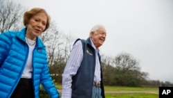 FILE - In this Feb. 8, 2017, file photo former President Jimmy Carter, right, and his wife Rosalynn arrive for a ribbon cutting ceremony for a solar panel project on farmland he owns in their hometown of Plains, Georgia, USA.