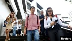 新加坡社運人士范國瀚(中)在一次庭審後離開新加坡法院。 (2017年11月29日)