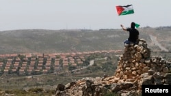 A protester waves a Palestinian flag in front of the Jewish settlement of Ofra during clashes near the West Bank village of Deir Jarir near Ramallah, Apr. 26, 2013.