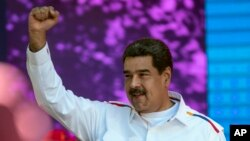 FILE - Venezuela's President Nicolas Maduro pumps his fist during a pro-government demonstration in Caracas, Venezuela, Feb. 12, 2019.