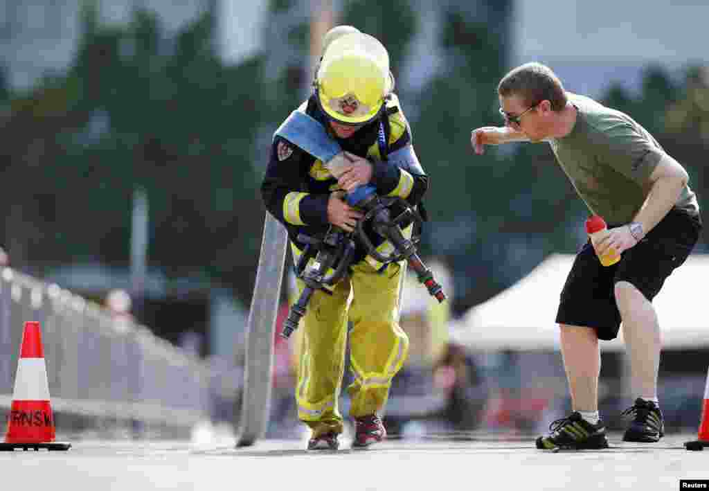 A teammate cheers a firefighter from South Africa as he competes in the Toughest Firefighter event at the 12th World Firefighter's Games in Sydney, Australia.