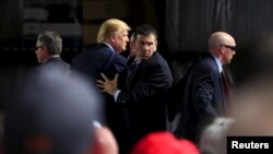 Secret Service agents surround U.S. Republican presidential candidate Donald Trump during a disturbance as he speaks at Dayton International Airport in Dayton, Ohio, March 12, 2016. (REUTERS/Aaron P. Bernstein)