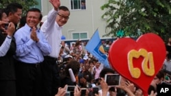 Opposition Cambodia National Rescue Party (CNRP) leader Sam Rainsy, right, accompanied by his party's Vice President Kem Sokha, second from right, waves to his party supporters during a public forum of the July 28 election result, in Phnom Penh, file photo.