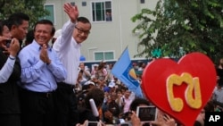 Opposition Cambodia National Rescue Party (CNRP) leader Sam Rainsy, right, accompanied by his party's Vice President Kem Sokha, second from right, waves to his party supporters during a public forum of the July 28 election result, in Phnom Penh, Cambodia, Monday, Aug. 26, 2013.