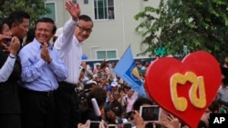 Opposition Cambodia National Rescue Party (CNRP) leader Sam Rainsy, right, accompanied by his party's Vice President Kem Sokha, second from right, waves to his party supporters during a public forum of the July 28 election result, in Phnom Penh, Cambodia, Monday, Aug. 26, 2013. Rainsy told thousands of supporters that his party will stage massive protests unless an independent committee begins investigating alleged irregularities in last month's election. (AP Photo/Heng Sinith)