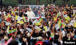 Pope Francis waves to Catholic faithful as he arrives to lead a mass at Kyite Ka San Football Stadium in Yangon, Nov. 29, 2017.