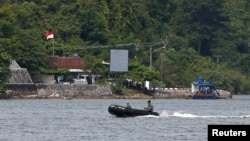 FILE - Indonesian military patrol in a small inflatable boat near a ferry boat dock on the prison island of Nusakambangan, in the background, in Central Java. March 3, 2015. Aman Abdurrahman is being held at Nusakambangan.