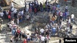 居民聚集在一枚汽車炸彈爆炸後的彈坑週圍
