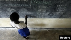Grace Debroha, a 13-year-old orphan, writes the names of body parts on a chalkboard at St. Jude's Orphanage, outside Gulu, Uganda, June 2007 file photo.