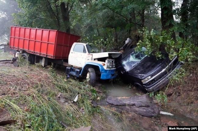 Un camion et une voiture se trouvent dans un ruisseau, dimanche 22 août 2021, après avoir été emportés par les eaux la veille à McEwen, Tennessee.