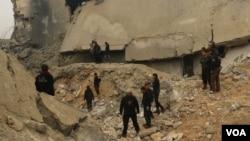 Miembros de la Defensa Civil de Siria y otras personas inspeccionan los daños a una mezquita en al-Jinah después de un ataque aéreo que dejó varios muertos civiles. Marzo 17, 2017.