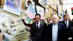 US Republican senator John McCain (R) walks with Abdul Hafiz Ghoqa, spokesman of the Libyan National Transitional Council (NTC), during his tour to the rebel headquarters in their eastern stronghold city of Benghazi , April 22, 2011
