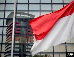 Gedung Komisi Pemberantasan Korupsi (KPK) terlihat dalam pantulan kaca melewati bendera merah putih di Jakarta pada 12 September 2017. (Foto: AFP)